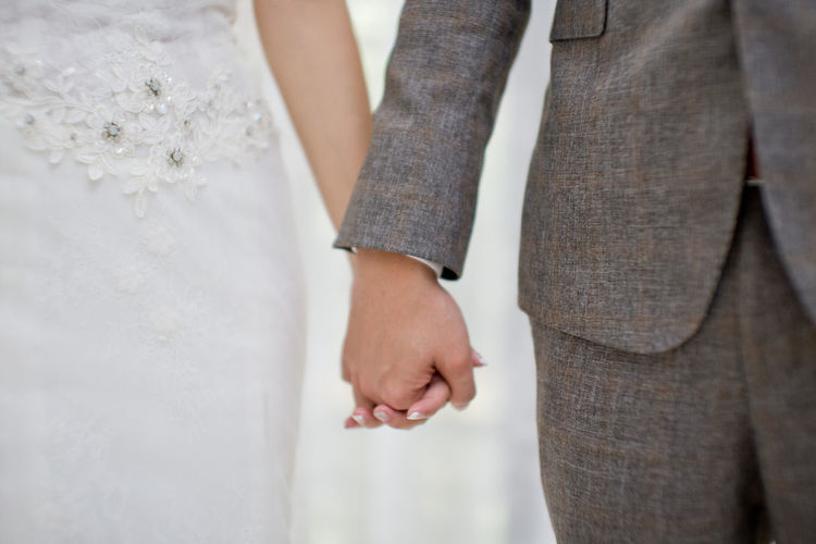 Close up groom and bride holding hands during wedding ceremony Adult Bonding Bride Celebration Couple - Relationship Event Hand Human Body Part Human Hand Life Events Love Midsection Newlywed People Positive Emotion Standing Togetherness Two People Wedding Wedding Ceremony Wedding Dress Women Human Connection #NotYourCliche Love Letter