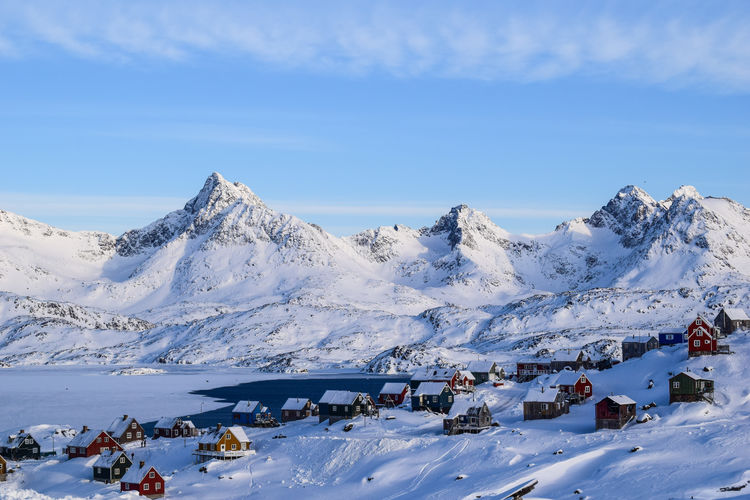 Houses on snowcapped mountains against blue sky