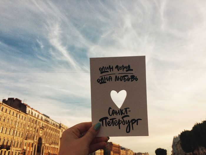 Text on hand holding heart shape against sky