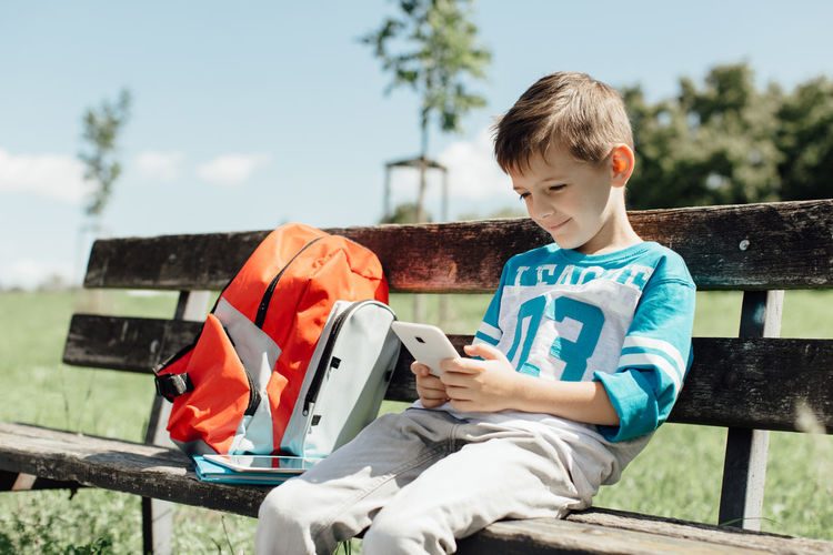 Schoolboy taking a break on a bench and playing with a mobile. 6 Years Alone Cellphone Copy Space Green Horizontal Mobile Phone Red School Bag Sitting Back To School Banch Boy Break Caucasian Child Day One Person Phone Call Play Real People Resting School Technology Young Student