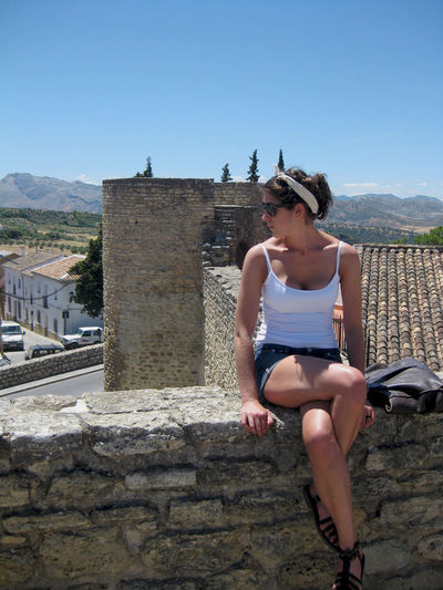 Young Woman Sitting On Stone Wall