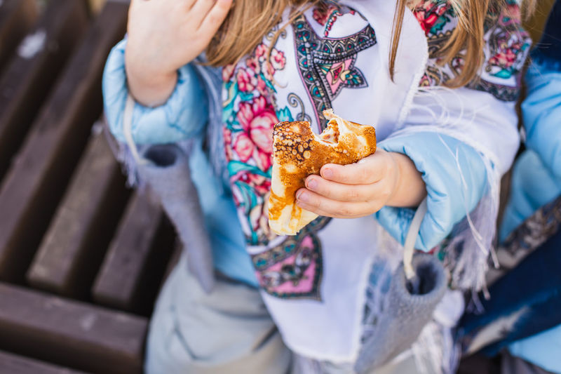 Midsection of girl holding food outdoors