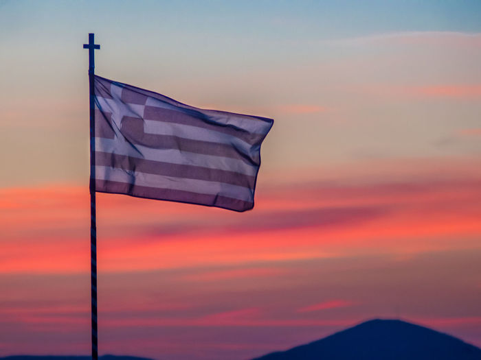 Low angle view of flag waving against dramatic sky during sunset