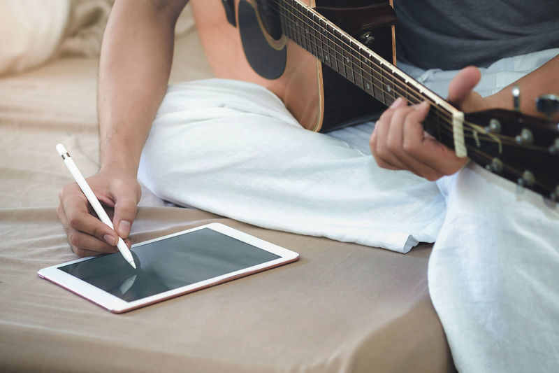 High Angle View Of Man Using Digital Tablet While Playing Guitar