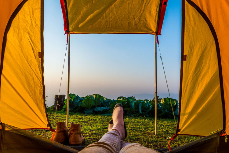 Low section of woman in tent on field against sky during sunset