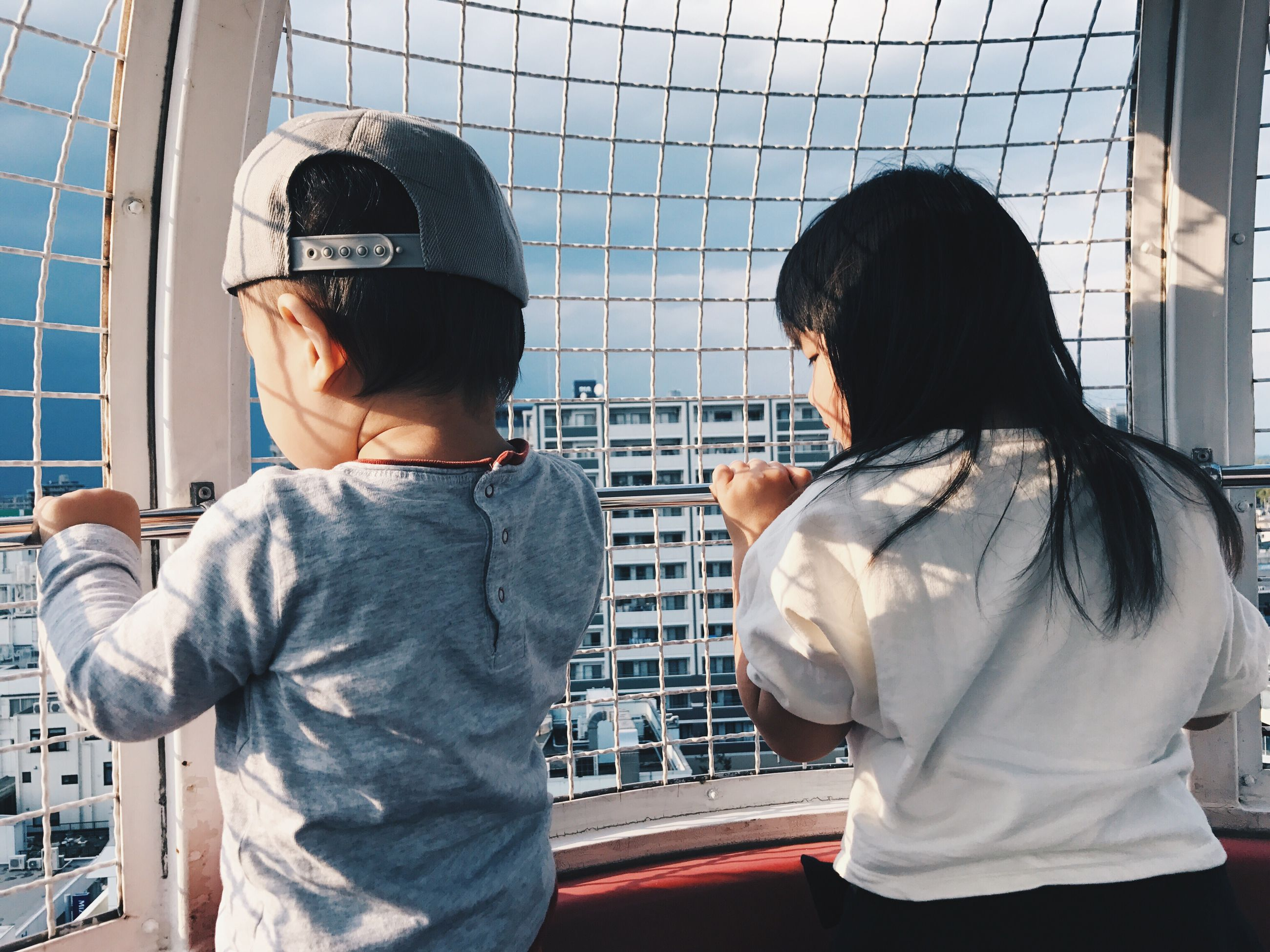 real people, two people, standing, indoors, rear view, childhood, day, casual clothing, boys, technology, cap, helmet, men, togetherness, young adult
