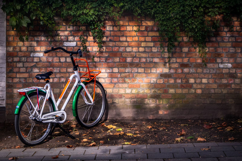 Travel Architecture Autumn Bicycle Bike Brick Brick Wall Building Exterior Built Structure City Day Footpath Land Vehicle Leaf Mode Of Transportation No People Outdoors Photography Plant Part Stationary Streetphotography Transportation Wall Wall - Building Feature Wheel