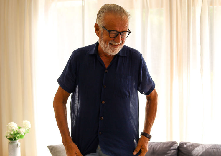 Man looking away while standing at home