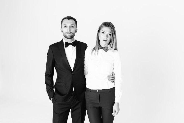 Portrait of confident elegant couple standing against white background