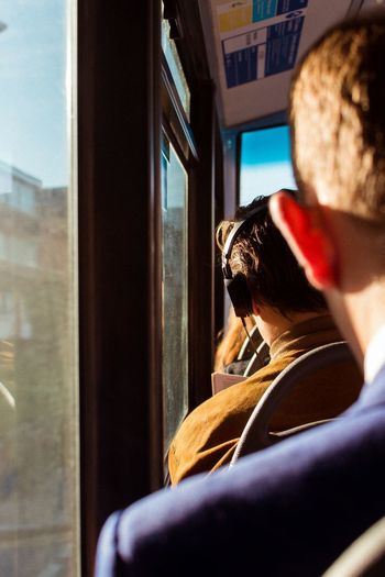 Rear view of man and woman seen through train window