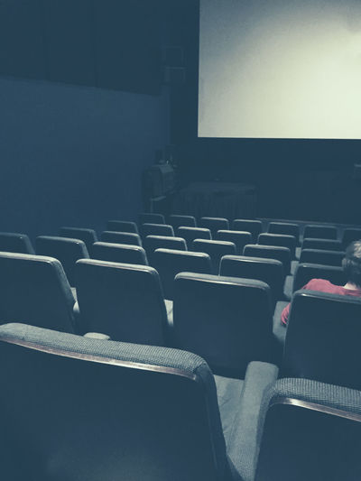 Man sitting and waiting in an almost empty cinema Audience Blank Chair Cinema Ciné Dark Empty Empty Places Entertainment Film Interior Movie Theatre  Movies Screen Seat Seats View Waiting Watching
