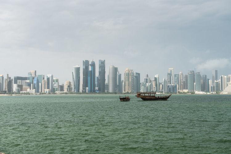 Boats In Sea Against Modern Buildings