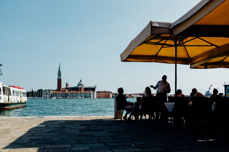 People at outdoors restaurant with church of san giorgio maggiore against clear sky