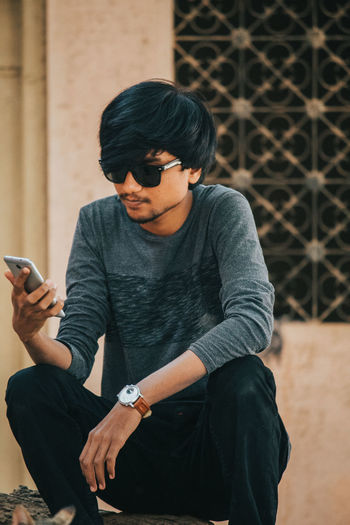 Young man wearing sunglasses while using mobile phone on tree trunk