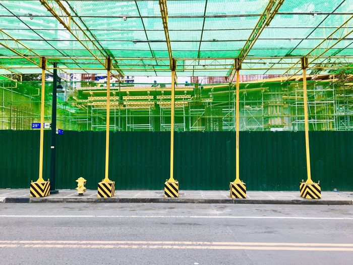 Scaffoldings, safety nets and temporary posts are installed near a construction site in Bonifacio Global City in Taguig, Metro Manila. Day Green Color Built Structure Indoors  Architecture No People Scaffolding Netting Ladders Walkways Pattern Geometric Scaffolding Construction Site Construction Green And Yellow  Philippines Taguig Bonifacio Global City