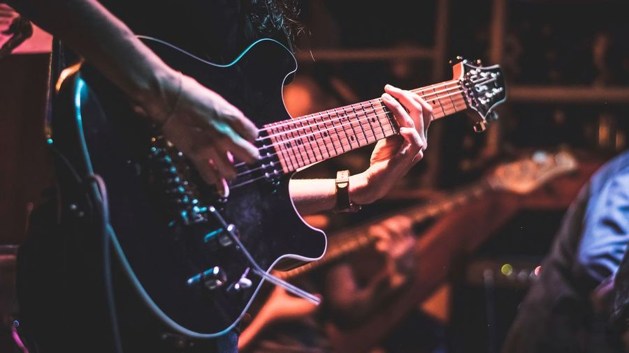 Music Musical Instrument Arts Culture And Entertainment Guitar String Instrument Performance Real People Musical Equipment Event Playing Focus On Foreground Light - Natural Phenomenon Lifestyles Illuminated Night Guitarist Stage - Performance Space Men Enjoyment People