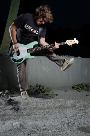 Young Man Jumping And Playing Bass Guitar At Night