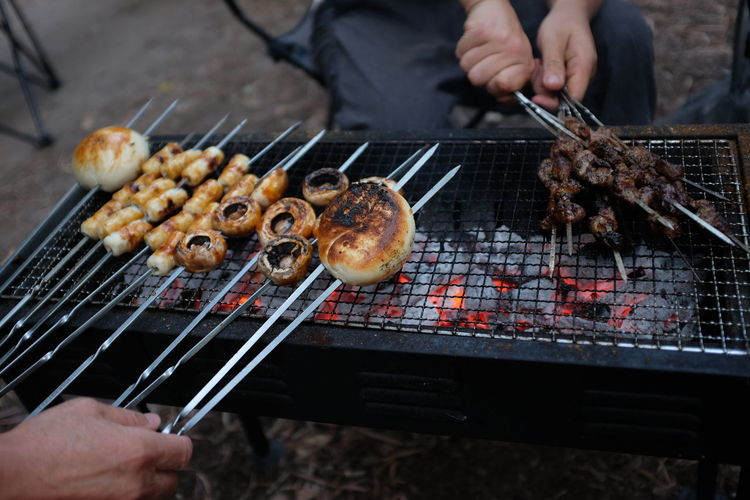 Friends preparing meat on barbecue grill