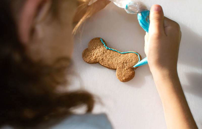 High angle view of girl icing cookie on table