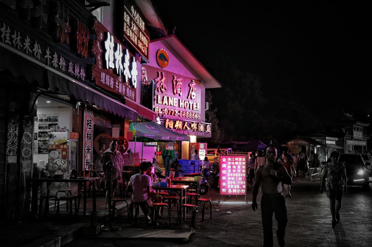 night, illuminated, large group of people, building exterior, architecture, real people, built structure, outdoors, restaurant, table, city life, chair, travel destinations, sidewalk cafe, men, women, lifestyles, city, sky, food, neon, people
