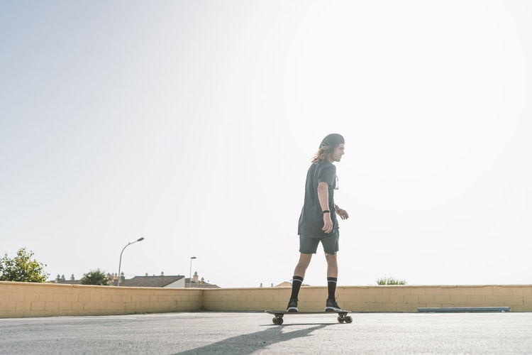 Side view of man skateboarding on street against clear sky