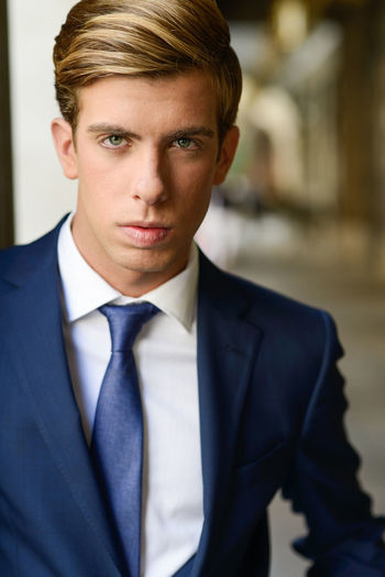 Portrait of young businessman standing in city