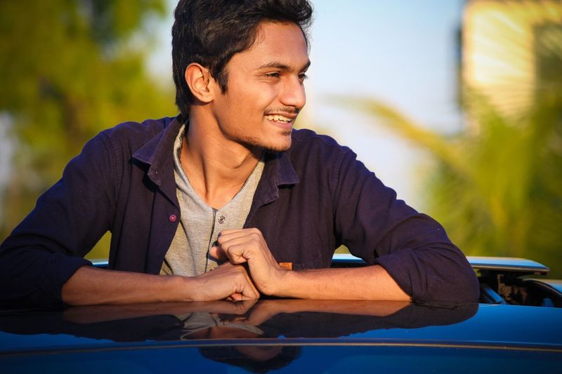Young Man Looking Away While Standing In Convertible Car