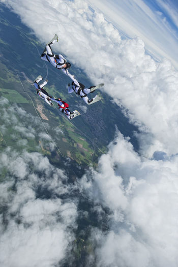 High angle view of people flying over mountain against sky