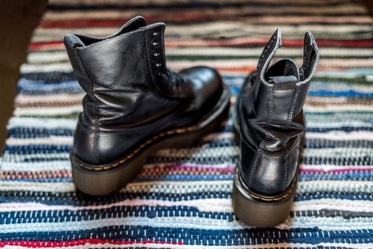 Back view of two robust, black ankle leather boots on a colorful rug as a concept of blisters Pair Back View Boots Gothic Heavy Leather Lifestyle Shiny Winter Young Youth Ankle Black Blister Concept Footwear Hipster Ill-fitting Punk Shoes Shoeshine Sole Style Work-boots Youthful