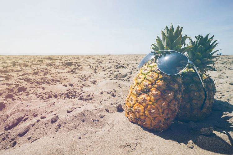 Close-up of sunglasses in pineapples on sand at beach