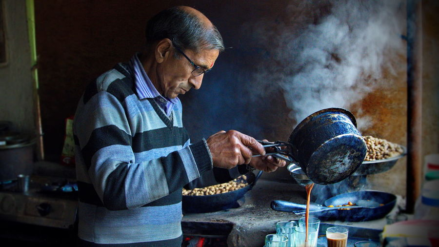 Tea Vendor Pouring Hot tea One Person Preparation  Real People Food And Drink Kitchen Utensil Concentration Mature Adult Senior Adult Preparing Food Waist Up Tea Vendor Side Lighting Garam Chai Tea Preparation The Magic Of Tea Indian Tea Poring Hot Tear Jageshwar Uttranchal Capture Tomorrow