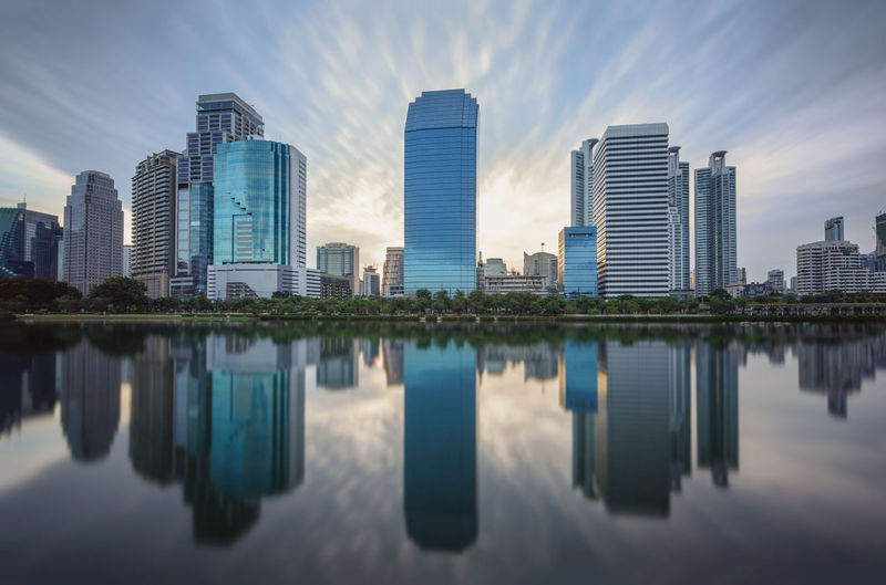 Reflection of buildings in lake against sky at city