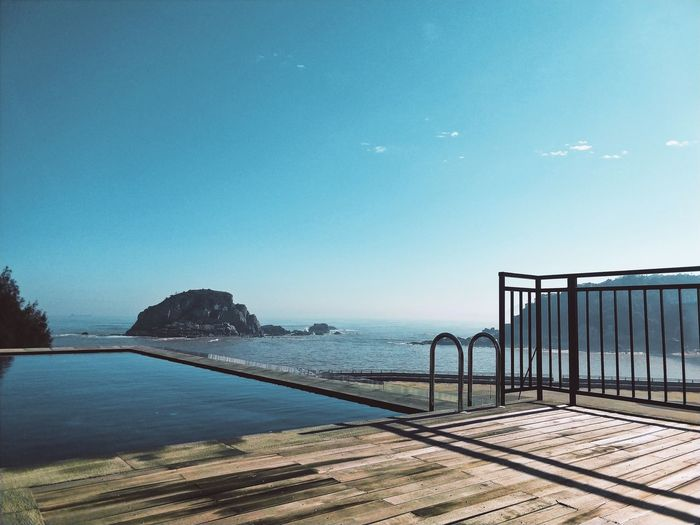 Scenic view of swimming pool by sea against clear blue sky