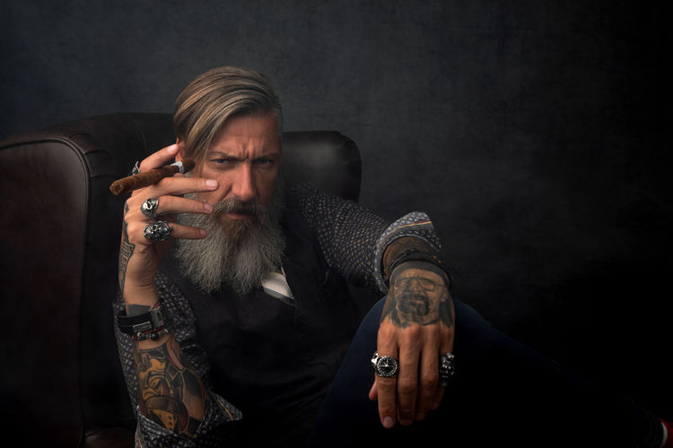 Portrait of a happy modern bearded businessman, who is sitting in an armchair with a cigar Beard Tattoo One Person Men Males  Indoors  Mature Adult Holding Tobacco Product Portrait Smoke - Physical Structure Smoking Issues Black Background Mature Men Hipster - Person Model Businessman Tattooed Cigarette  Smoking Relaxing Armchair Manager Lifestyles Looking At Camera