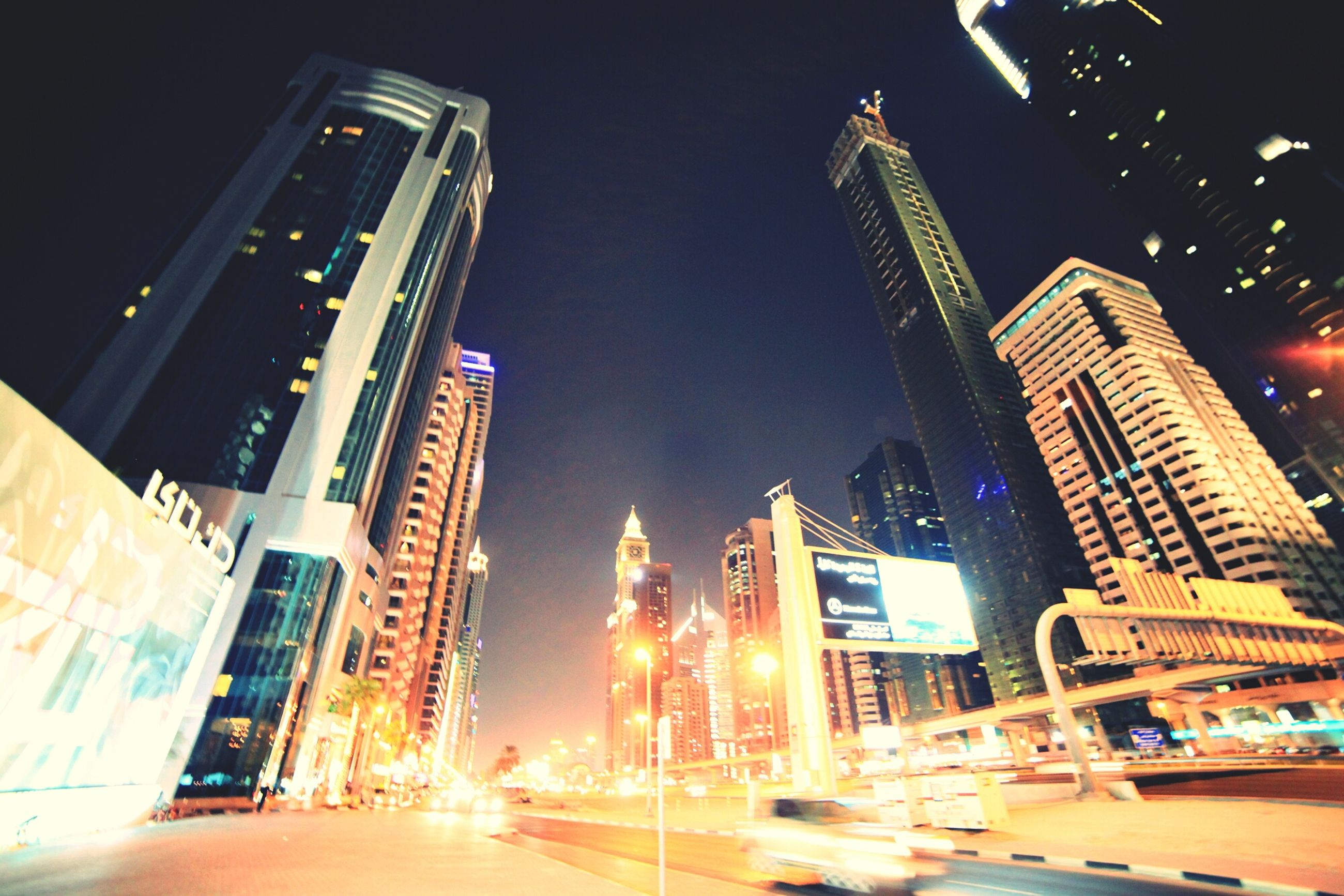 illuminated, architecture, building exterior, night, built structure, city, skyscraper, tall - high, modern, tower, office building, low angle view, street light, city life, capital cities, building, street, travel destinations, sky, financial district