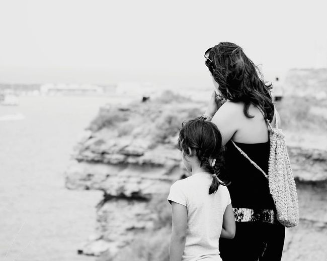 Rear view of mother with daughter standing on cliff