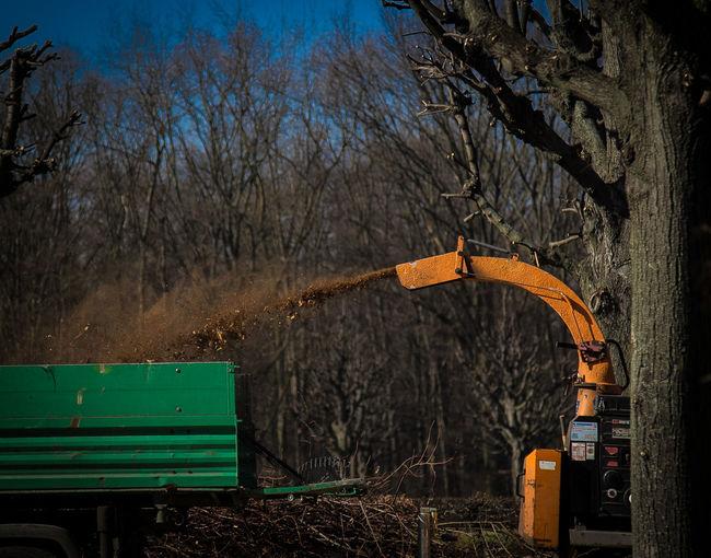Gardening equipment spraying dirt against trees on field