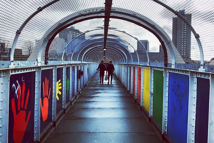 Rear View Of Men Walking On Bridge