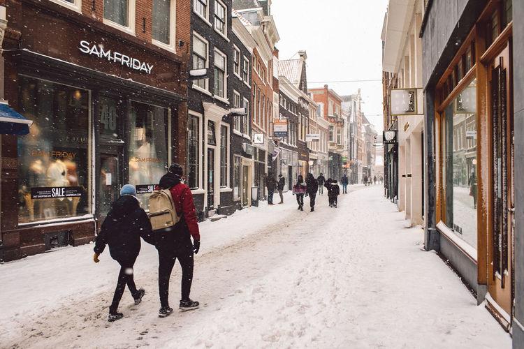 People walking on street amidst buildings in city during winter