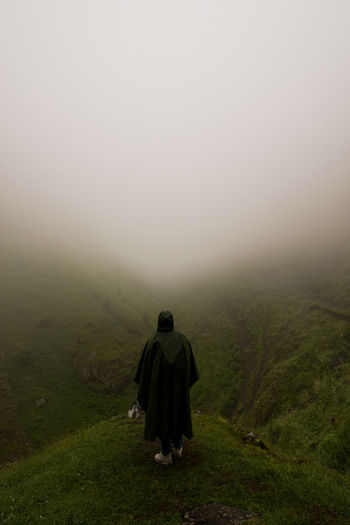 Rear view of man on landscape against sky during foggy weather