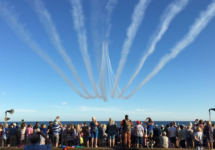 People looking at airshow over sea