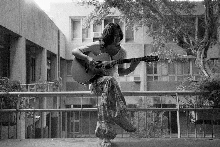 Woman playing guitar while sitting on railing