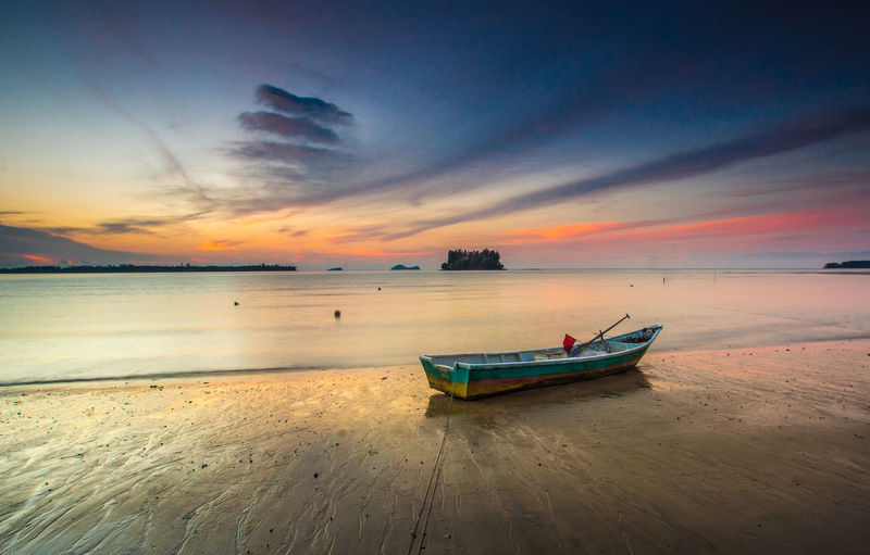the boat at beach during sunset Nautical Vessel Transportation Sky Water Sea Mode Of Transportation Sunset Scenics - Nature Beach Land Cloud - Sky Beauty In Nature Tranquility Horizon Horizon Over Water Moored Tranquil Scene Nature Orange Color No People Fishing Boat Anchored