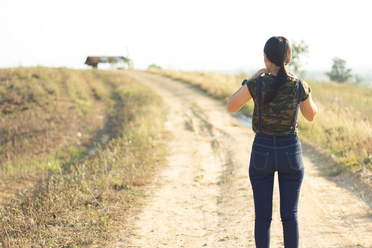 Woman Standing On Dirt Road