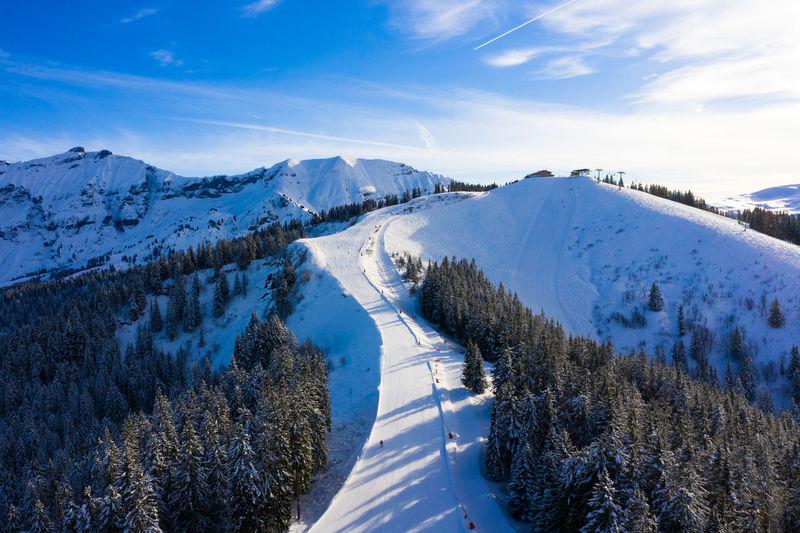Scenic view of snow covered ski resort against sky