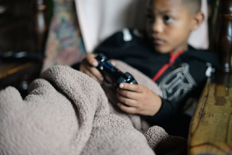 Boy playing video game at home