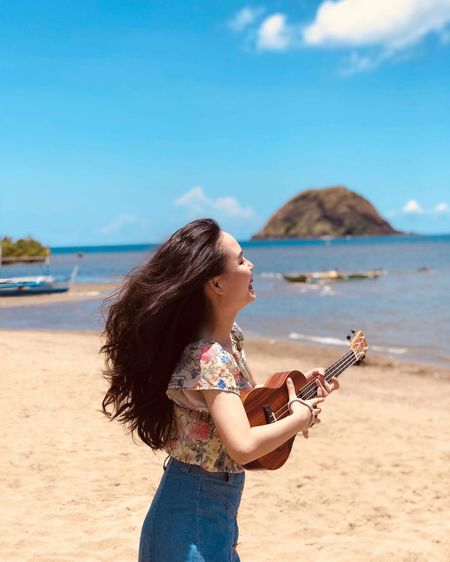Side view of woman holding ukulele while standing at beach