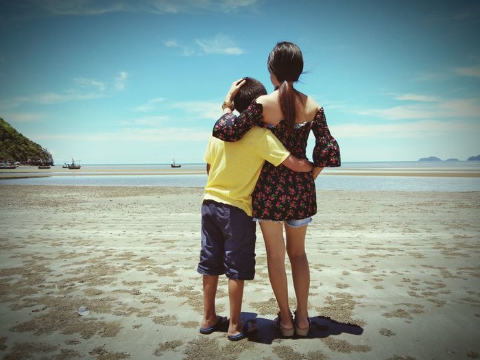 Rear view of mother and son standing at beach during sunny day