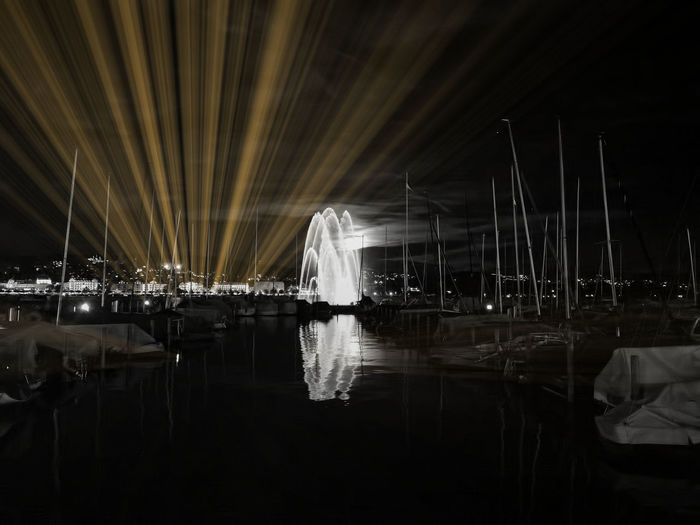Sailboats moored in illuminated harbor against sky at night