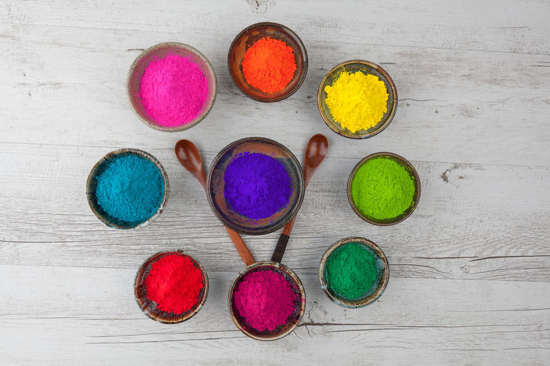 Directly above view of colorful powder paints in bowl on wooden table